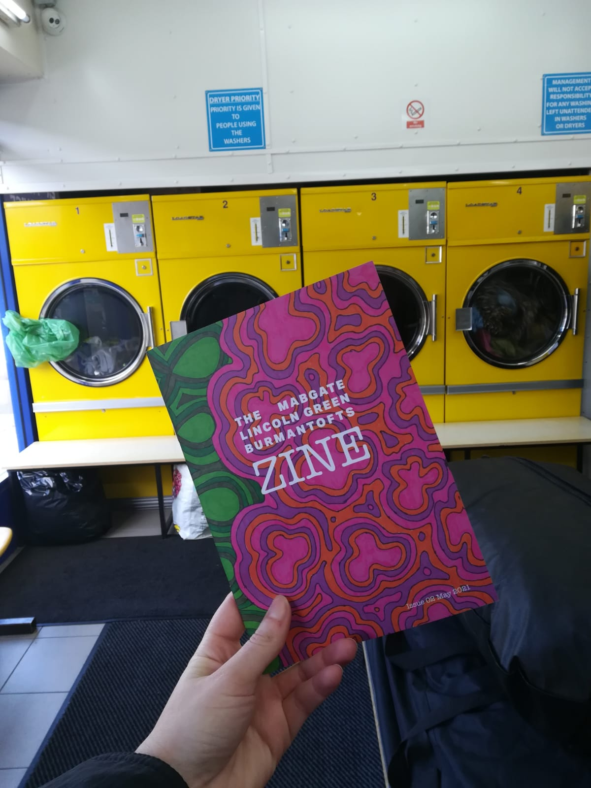 A hand holding Zine in Lincoln Green laundrette