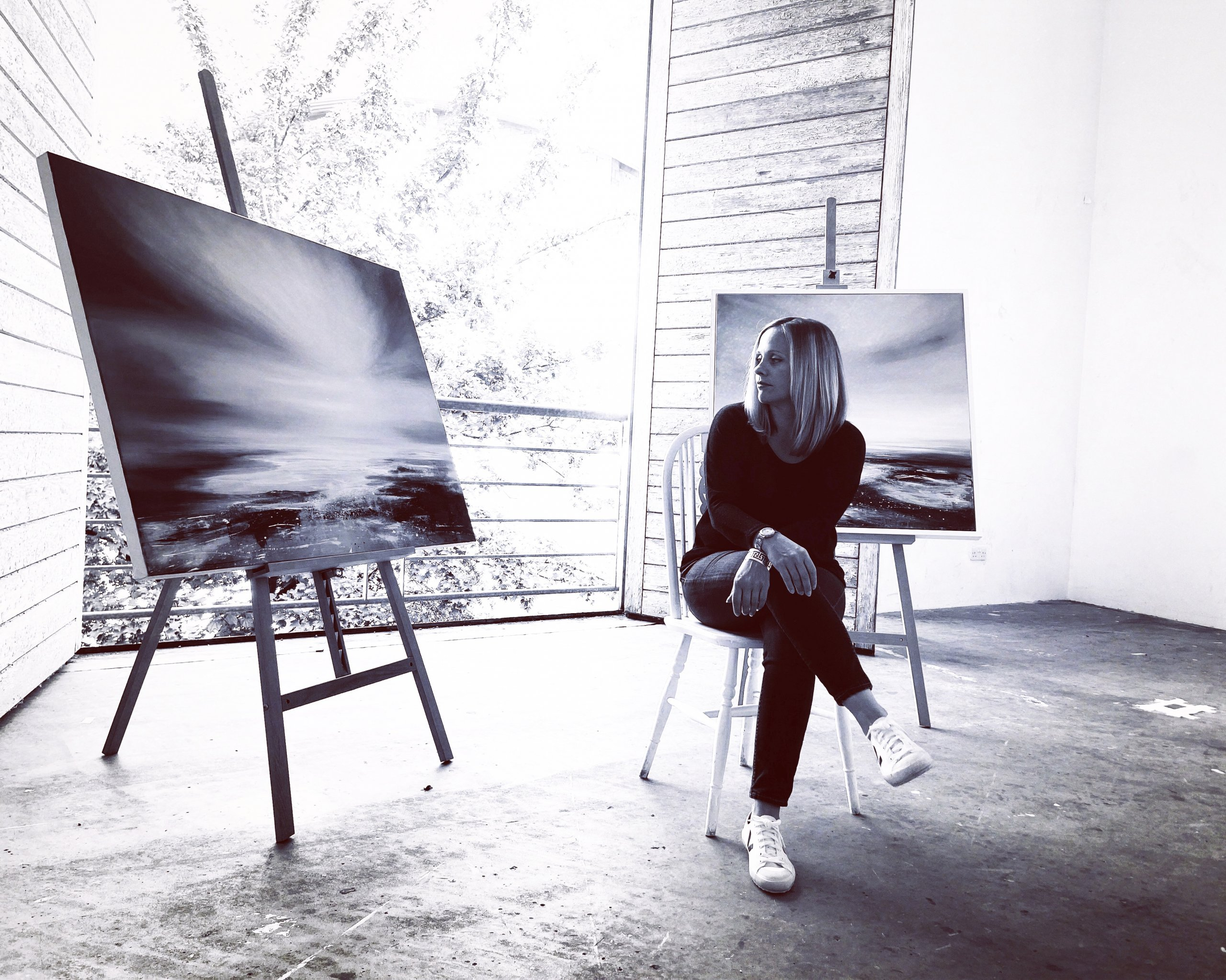Black and white photograph of Tessa Houghton sat between two of her paintings in Patrick Studios at East Street Arts